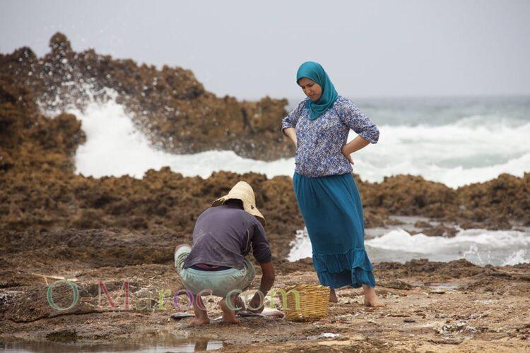 Une femme surveille la préparation de son poisson par un pêcheur, dans les rochers