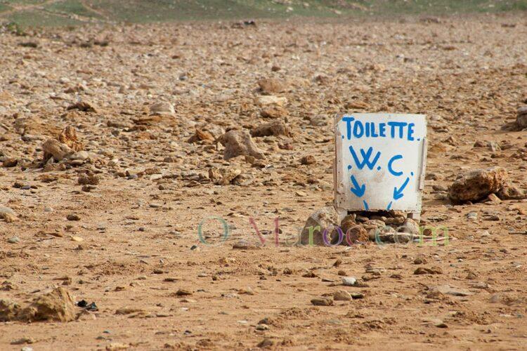 Un trou dans le sable avec une pancarte
