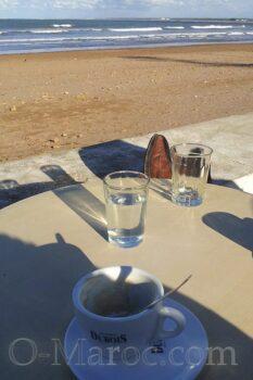 Café et verre d'eau face à la mer
