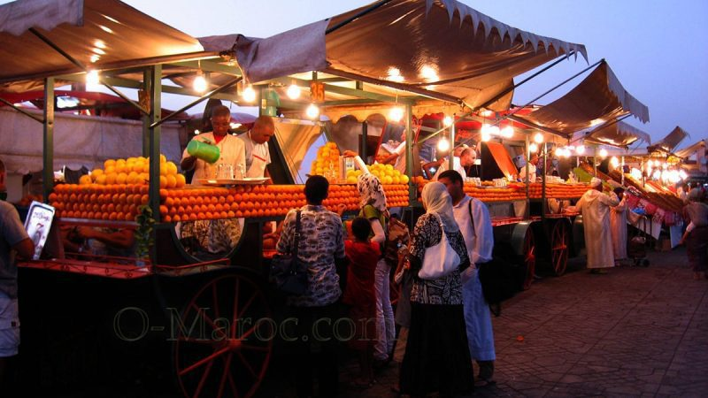 Au soleil couchant, un groupe de marocains achète des jus d'orange