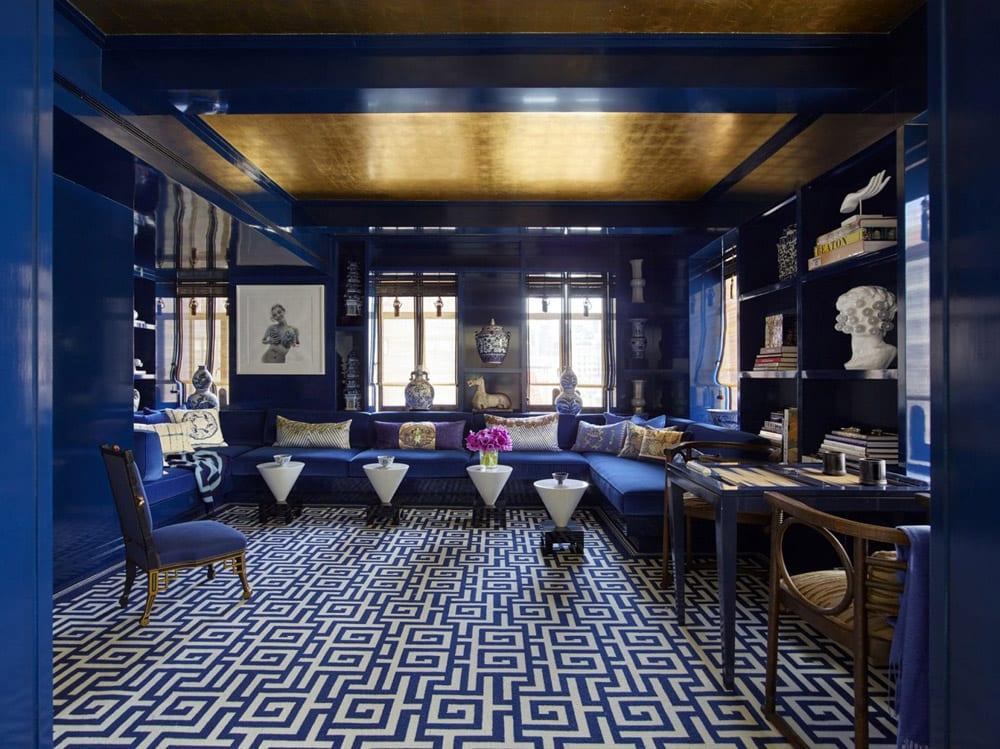 Une pièce bleu intense avec un tapis aux motifs sinisants, une banquette organisée comme un salon marocain et des petites tables.