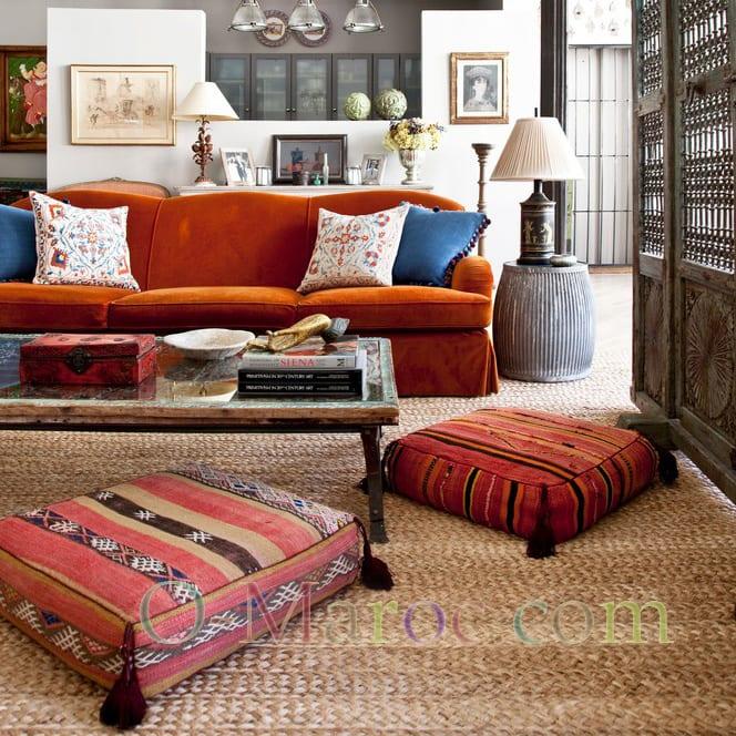 Coin salon avec un canapé, une table basse et deux grands coussins marocains.