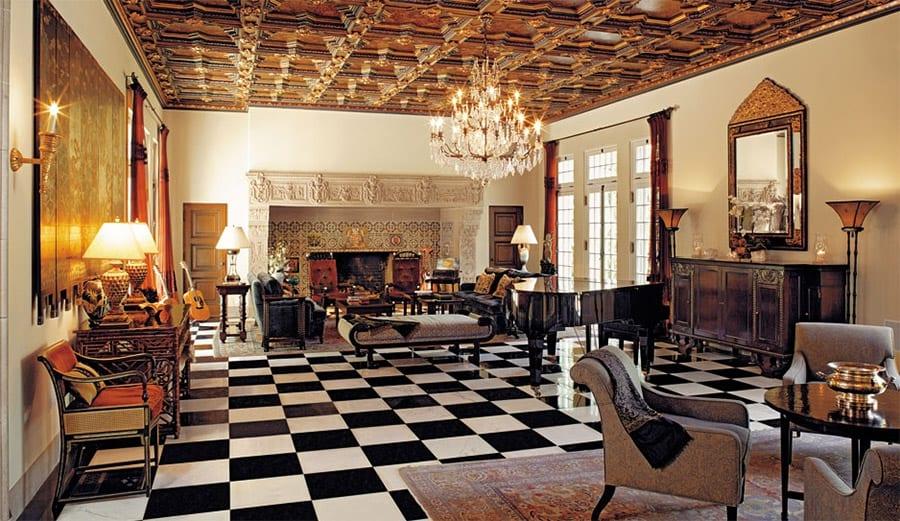 L'immense salon de réception au carrelage blanc et noir et aux caissons de bois peints