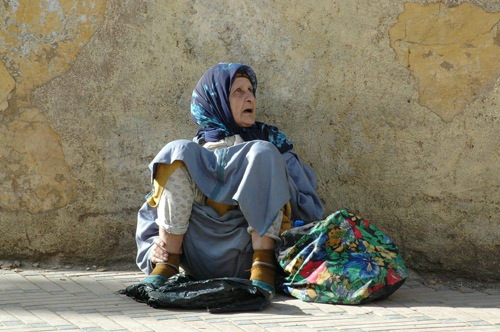 Assise par terre, une femme âgée mendie