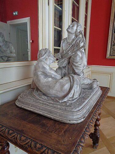 Une femme nue joue de la lyre devant un homme nue, statue de Bartholdi