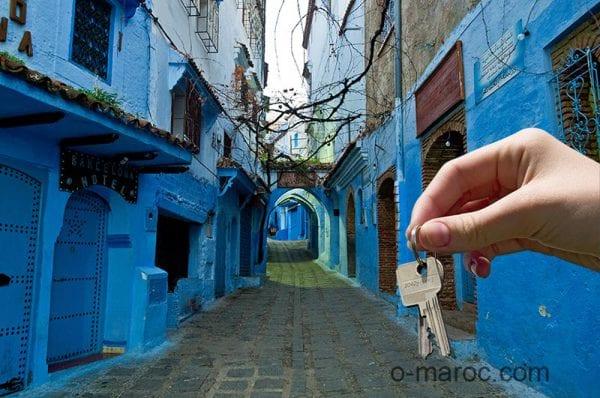 Main donnant des clés sur fond de medina de Chefchaouen