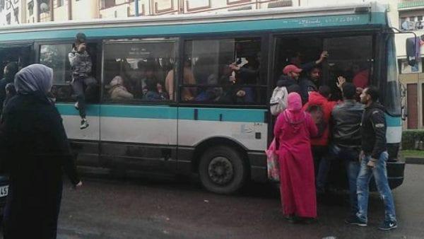 Un bus bondé, avec un passager qui sort par une fenêtre