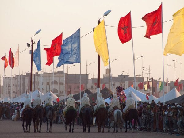 Cavaliers défilant devant des drapeaux marocains et des pavois bleus et jaunes