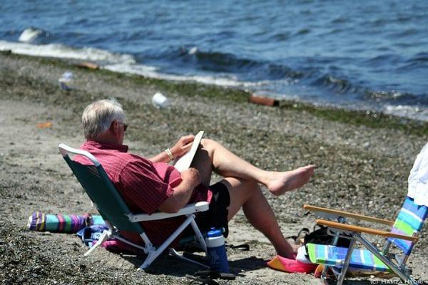 Retraité en train de lire sur une plage
