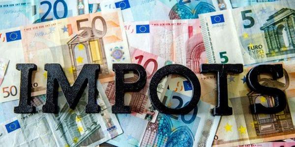 """Le mot """"impots"""" sur fond de billets en euro"""