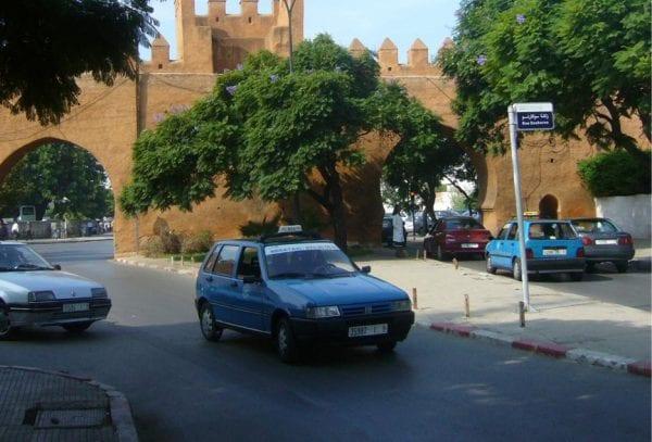 Un taxi bleu sort d'une des portes de la muraille