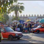 De nombreux petits taxis rouges devant les murailles du souk à Agadir